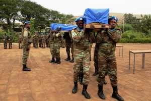 Malian and MINUSMA soldiers carry the flag-draped coffins of two U.N. soldiers killed in last Saturday's bomb attack in Kidal, during their funeral in Bamako December 18, 2013. A suicide bomber killed two Senegalese U.N. peacekeepers and destroyed the only operating bank in the northern Malian town of Kidal last Saturday, a day before a second round of parliamentary elections. REUTERS/Adama Diarra (MALI - Tags: CIVIL UNREST MILITARY POLITICS CONFLICT)